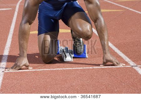 African American male athlete at starting block in race track