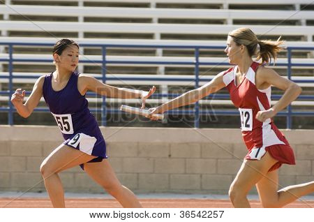 Female runners passing baton in relay race
