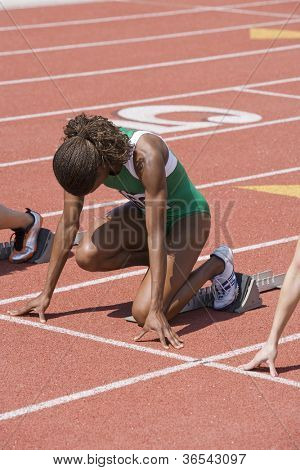 African American Female athlete with competitors at starting line