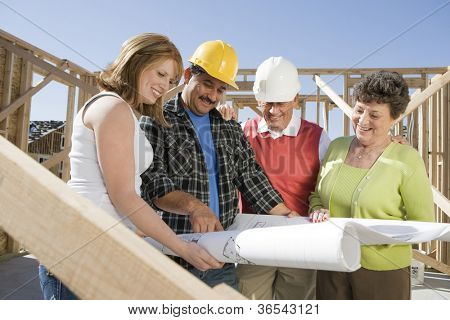 Happy construction workers reviewing blueprint on construction site