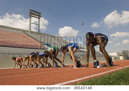 Multiethnic female athletes at starting line on race track