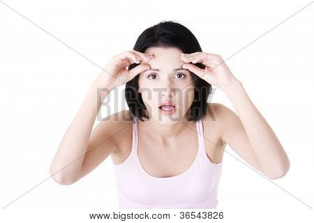 Beautiful shocked woman checking her wrinkles on her forehead