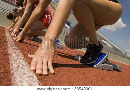 Hands of female athletes at starting line on race track