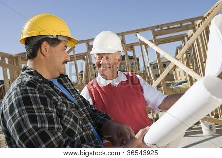 Construction workers reviewing blueprint on construction site