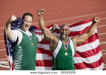 Male athlete with medal and American flag on track and field