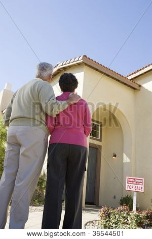 Happy senior couple standing in front of their new home