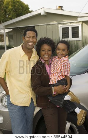 African American couple with baby standing in front of their house