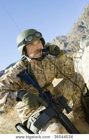 Soldier phoning with assault rifle on a mission