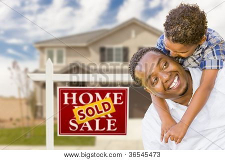 Happy Mixed Race Father and Son In Front of Sold Real Estate Sign and New House.