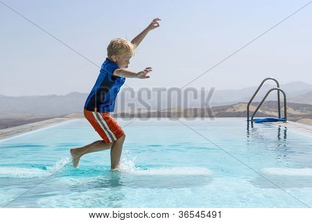 Young boy trying to keep his balance whilst jumping from one block to another in an infinity pool