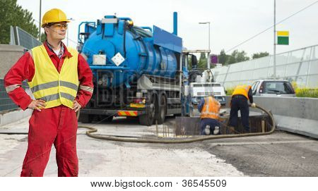 Civil engineer posing in front of road works, where a concrete foundation is poured into the foundation of the road