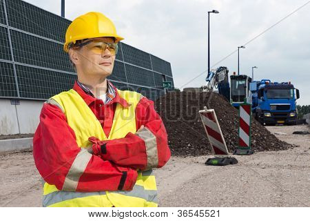 Road construction worker, wearing an overall, safety vest and other safety precautions, overlooking the building site, with a dump truck and digger in the background, behind a pile of gravel