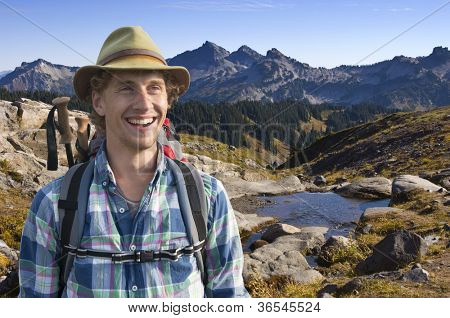 Smiling mountain guide with a backpack and walking stick on his back on a sunny afternoon in the middle of nowhere