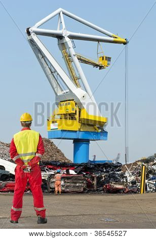 Engineer, wearing overalls, safety shoes, a reflective vest and hard hat, standing with his hands behind his back, holding a CB radio, looking out at a huge  harbor crane and the car graveyard