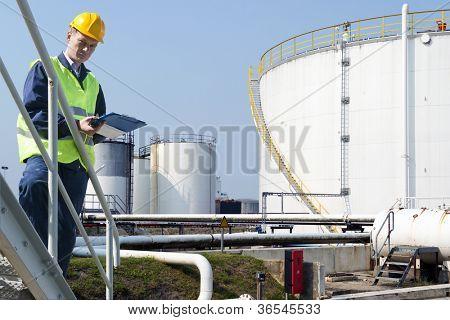 Engenheiro com uma prancheta, tomar notas, da qualidade e estado de silos de óleo de uma petroquímica indu