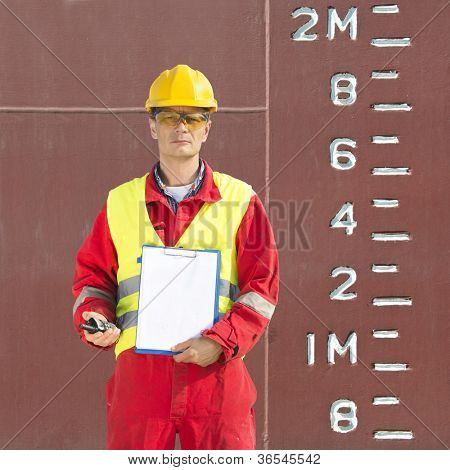 Docker, standing with a clipboard with a blank page and a cb radio next to the scales and height indication of the hull of a industrial ship