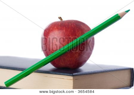 A Red Apple With Green Pencil On Top Of Many Books