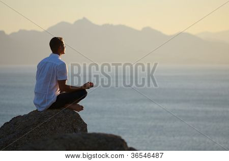 Guy sitting on a rock in the lotus position and looking at the setting sun