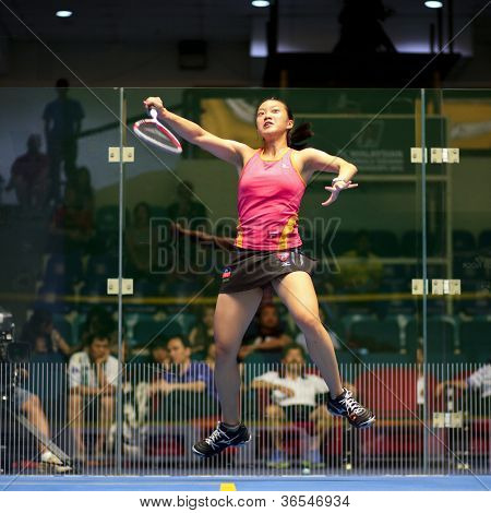 KUALA LUMPUR - SEPTEMBER 01: Low Wee Wern (red) smashes the ball in her match at the TC Malaysian National Squash Championships 2012 played at the Arena Nicol David, Malaysia on September 01, 2012.