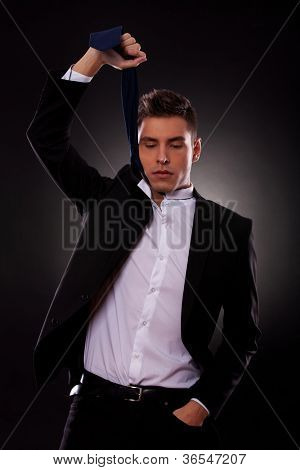 Young businessman in suit holding up tie to strangle himself