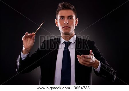 Portrait of a young conductor directing his orchestra. Leadership concept. Young businessman directing with a conductor's stick.
