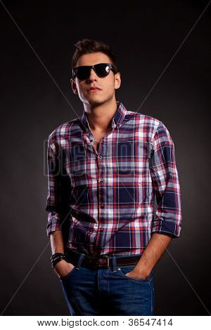 Casual young man standing with both hands in pockets. He is wearing sunglasses and a squared shirt and has a cocky attitude look. On dark background