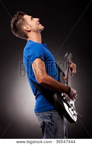 side view of a guitarist playing his electric guitar on black background