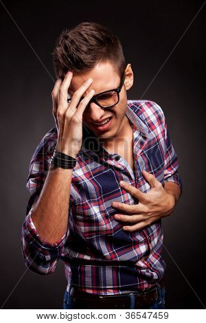Angry young man doing a frustration gesture over a black background