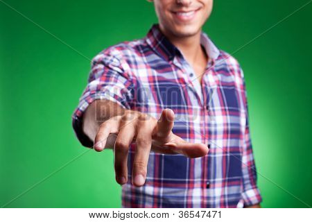 cropped picture of a young man pointing to the camera or pushing animaginary button, on green background