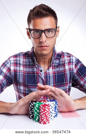 young poker player with eyeglasses going all in, on gray background