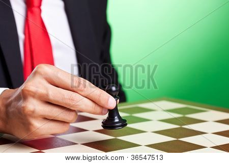 business man moving a pawn, over green background
