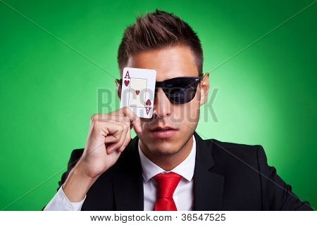 Young business man with sunglasses covers one eye with an ace of hearts. Over green background.