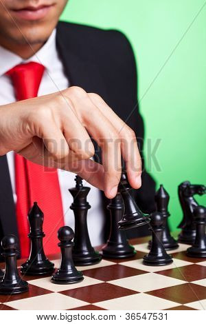 business man playing chess game selective focus black makes first move. on green background