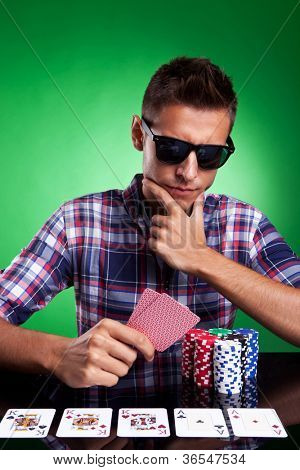 Casual dressed young man looking thoughtfully at his poker hand, with full house on the poker table. Over green background