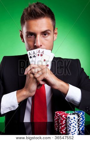 Young businessman card player covering his mouth with four aces, on green background