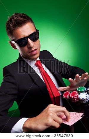 Confident young business man going all in, over green background