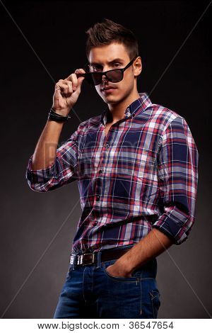 Serious young casual man taking down his sunglasses. Young casual man looking at the camera over his sunglasses . On black background.