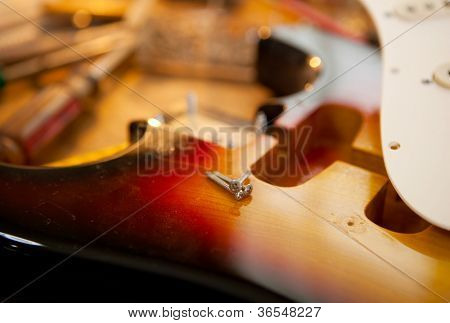Guitar on guitar repair desk. Electric guitar on a guitar repair work shop. Neck and pickguard detached. Double cutaway solid body guitar, sunburst color. Shallow depth of field.