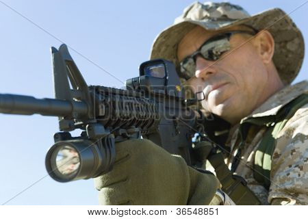 Soldier in sunglasses with assault rifles on a mission