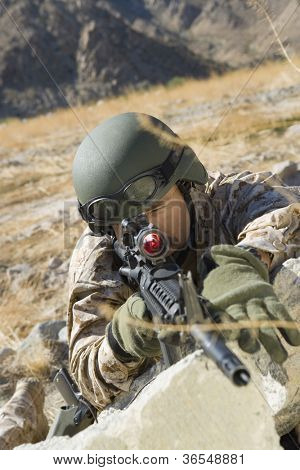 Soldier pointing with assault rifle on a mission