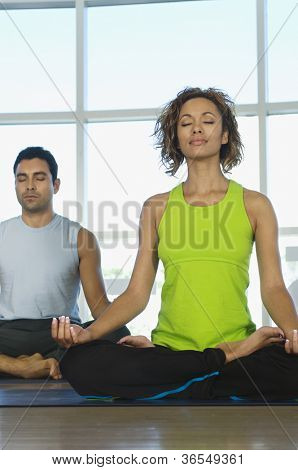 Woman and man meditating in lotus position