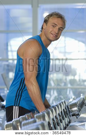 Man stands in front of dumbbells on rack at gym