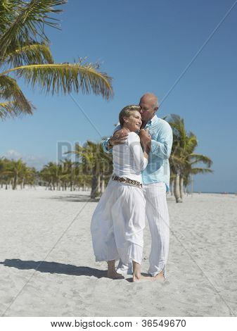Senior couple embracing at beach on sunny a day