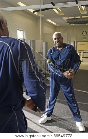 Senior man looking into the mirror during exercising in gym