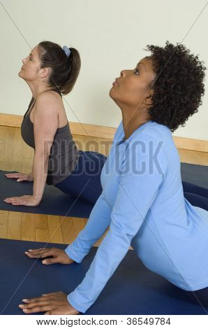 Two women practicing yoga on a mat