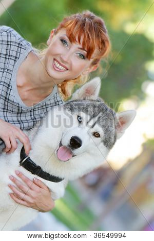 young happy woman with dog haski outdoors