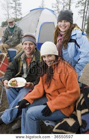 Family having food at campfire