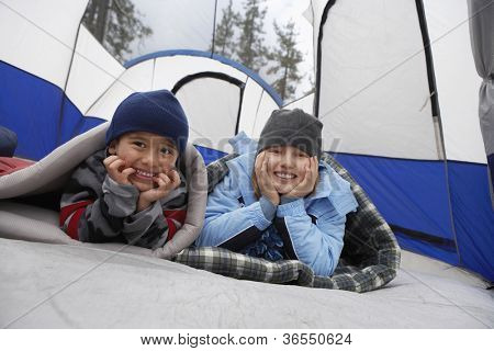 Children in winter clothing inside tent