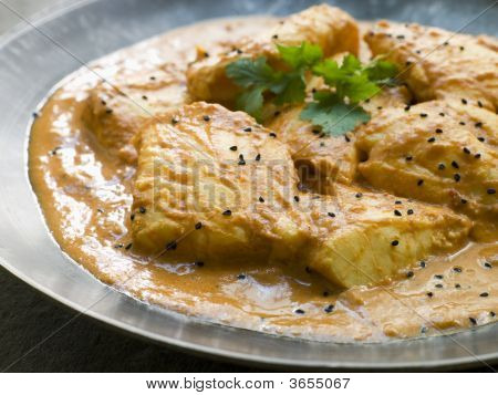 White Fish Molee On A Pewter Plate With Nigella Seeds