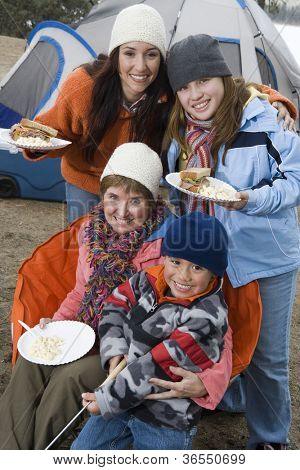 Happy family having food at campfire